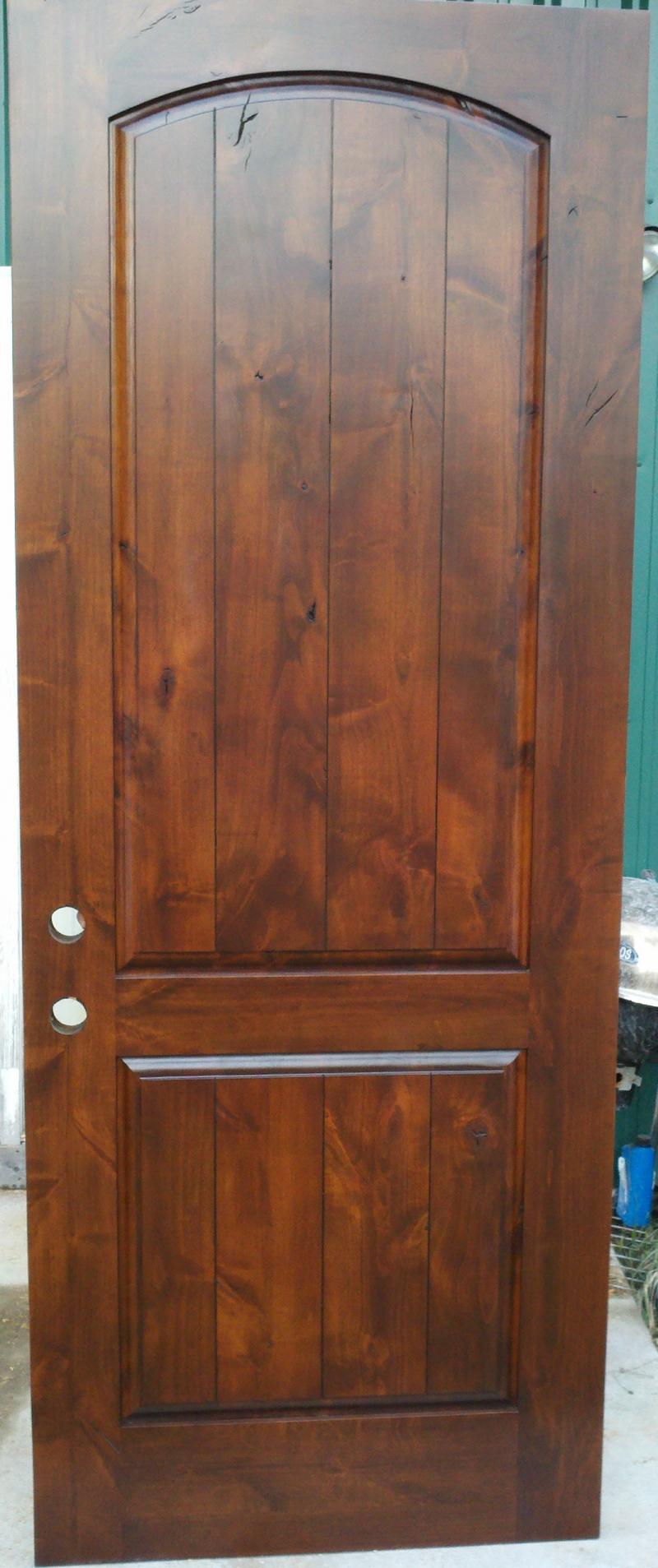 Knotty alder arch top rail raised panel door.